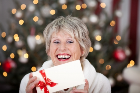 christmas bonus: Laughing elderly lady with an Xmas gift voucher holding the blank white envelope decorated with a red ribbon in her hand as she sits in front of the Christmas tree