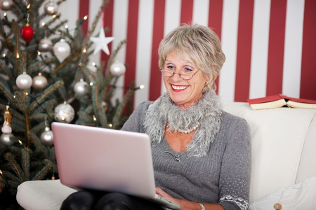 Attractive glamorous senior woman sitting in her living room in front of a decorated Christmas tree using a laptop, red and white themed photo