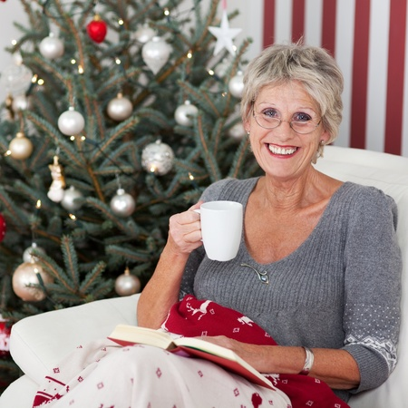 Smiling elderly woman with a cup of tea and a book relaxing in front of a decorated Christmas tree in her living room photo