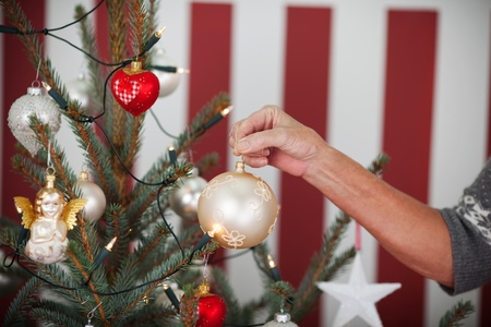 decorating christmas tree: Hand of an older woman decorating a Christmas tree with a large white bauble hanging it on the branch, red and white themed with striped background