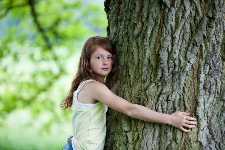 preocupacion: Retrato de pre adolescente abrazando árboles en el parque