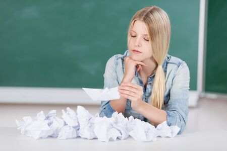 block note: Attractive young blond student or teacher having problems at school sitting in front of a large pile of crumpled paper reading a single slip of paper in her hand