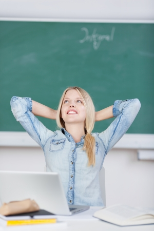 Relaxed female student with hands behind head day dreaming while sitting at desk photo