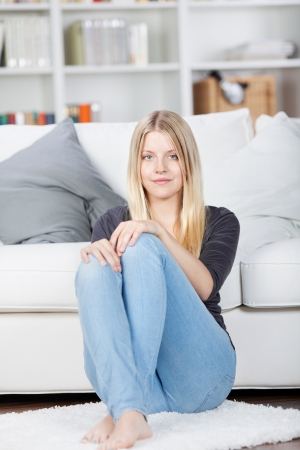 Young woman sits on the floor in her livingroom photo