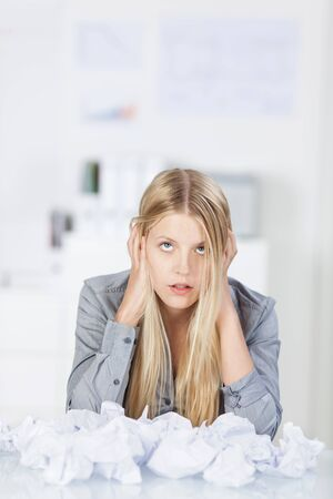 inefficient: Chaos in the office as an overworked stressed secretary or businesswoman suffers mental block and begins balling paper into a crumpled heap on her desk Stock Photo