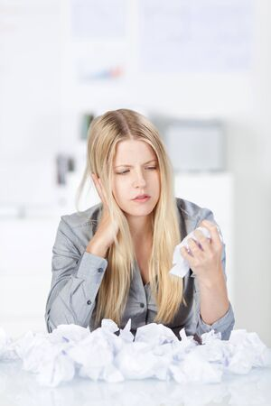 writers block: Businesswoman with a mental block unable to come up with a new strategy or solve a problem crumpling paper in her hand to add to the pile in front of her in frustration