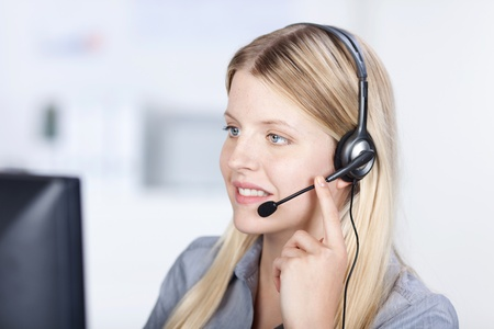 costumer: Female customer service executive using headset while conversing in office Stock Photo