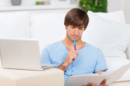 young man with laptop and file learning at home Stock Photo - 21109374