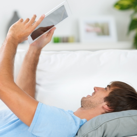 relaxed man reading an ebook on the sofa photo