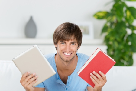 smiling man showing book and ebook at home photo