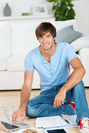 smiling young man sitting on the floor with laptop photo