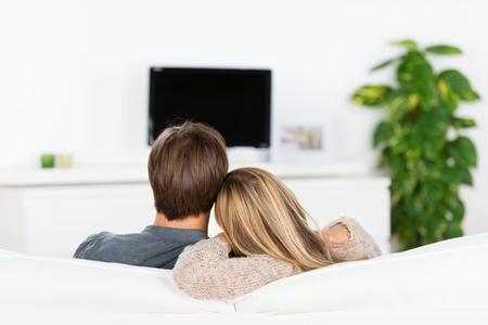 jong koppel zittend op de bank, tv kijken