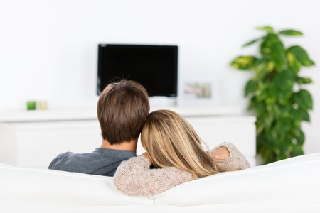 watches: young couple sitting on sofa, watching tv Stock Photo