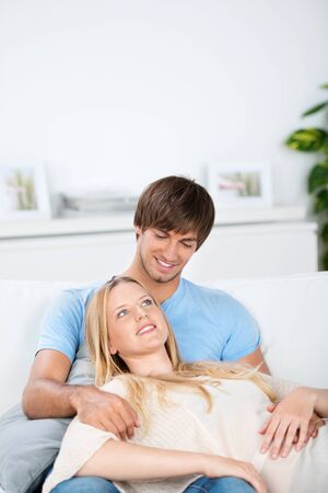20s  closeup: relaxed couple sitting on the sofa, hugging Stock Photo