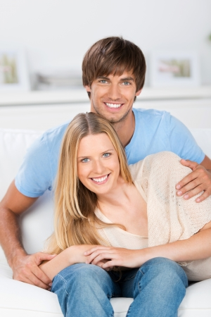 20s  closeup: amorous, smiling couple sitting relaxed at home Stock Photo
