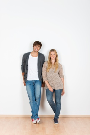 happy young couple: relaxed, smiling couple leaning against the wall