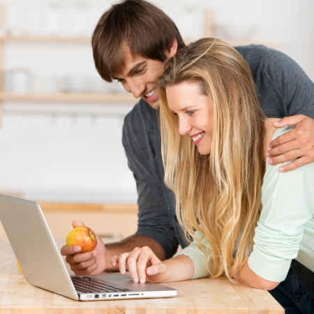 laptop stand: couple in the kitchen looking on laptop Stock Photo