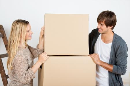 batch: pareja est� de pie debajo de un lote de cajas Foto de archivo