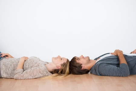 relocation: couple lying head to head in an empty room Stock Photo