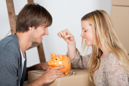 couple moving and thowing coins in a piggybank Stock Photo - 21109459