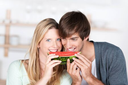 smiling young couple eating fresh melon together photo