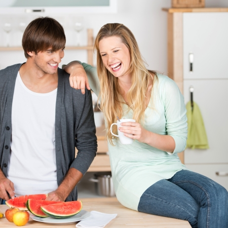 young couple working in the kitchen and having fun photo