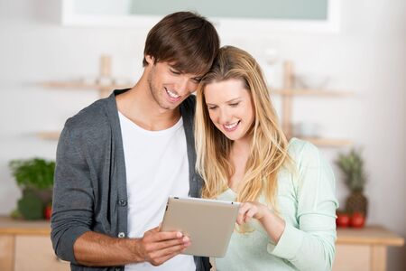 couple looking at tablet in the kitchen photo