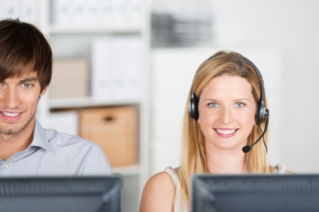 two smiling colleagues with headset in the office photo