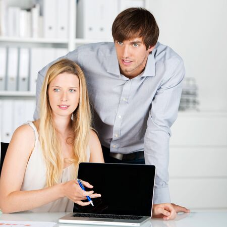 business man and woman presenting on laptop photo