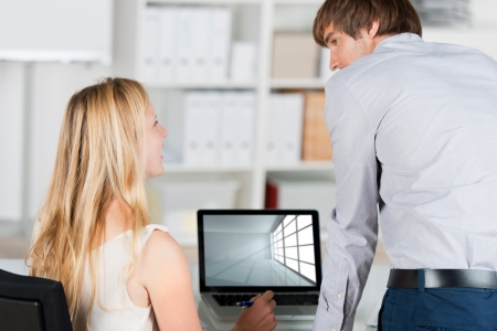 men at work: business man and woman with laptop in the office Stock Photo