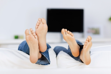 couple lying barefeet on sofa in front of tv