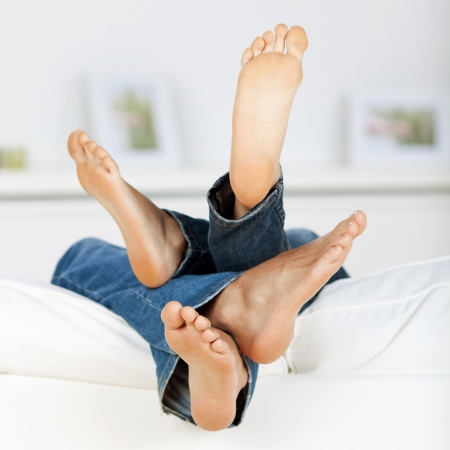 man and woman lying barefeet on sofa photo
