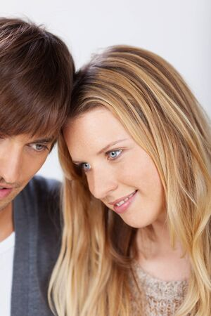 young couple smiling: smiling, blonde woman leaning on her boyfriend