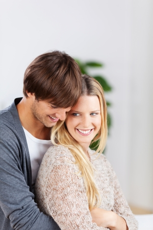 femal: man and woman hugging and laughing at home