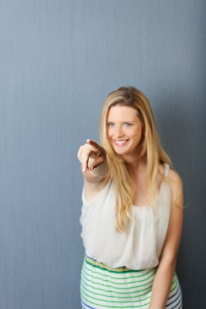 cheerful young woman pointing finger on someone photo