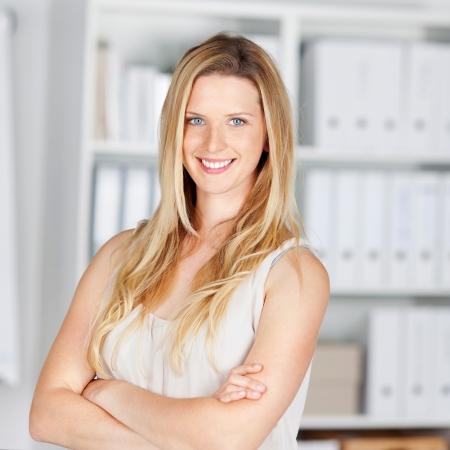 femme blonde: femme blonde souriante au bureau, les bras croisés