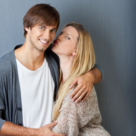 portrait of smiling man and woman kissing photo