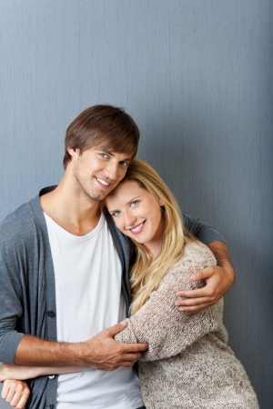 embracing young couple smiling in front of grey wall Stock Photo - 21109565