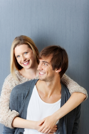 embracing: man and woman smiling and hugging in front of grey wall