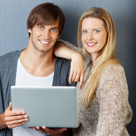 couple with laptop in front of grey wall photo