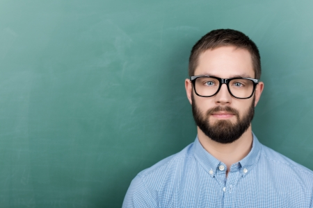 Portrait of confident young male student wearing eyeglasses against chalkboard Stock Photo - 21109582