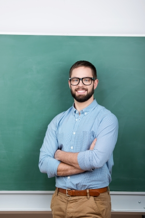 Portrait of confident young male student wearing eyeglasses against chalkboard Stock Photo - 21109583