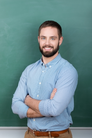 Portrait of confident young male professor with arms crossed standing against chalkboard Stock Photo - 21109584