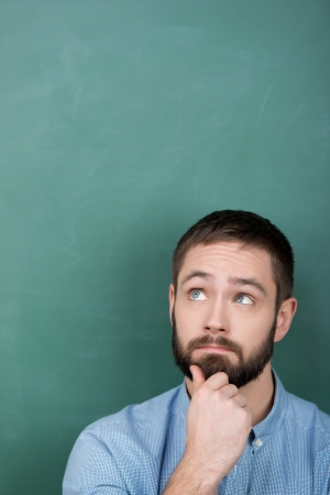 Thoughtful young male professor with hand on chin looking up against chalkboard