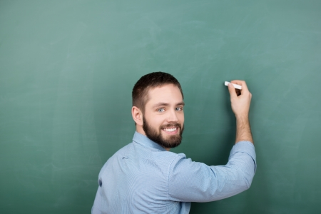 looking over shoulder: Portrait of happy young male professor writing on chalkboard while looking over shoulder