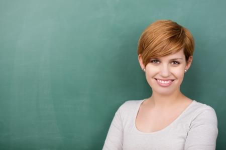 Portret van vertrouwen vrouwelijke hoogleraar lachend tegen schoolbord Stockfoto