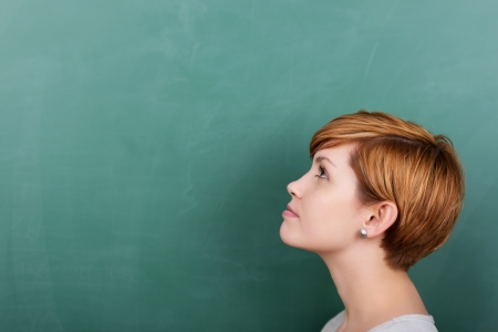 in thought: Thoughtful female student looking at a chalkboard Stock Photo