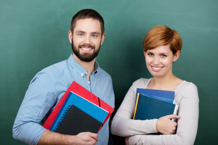 Portrait of confident male and female teachers holding books and files against chalkboard photo