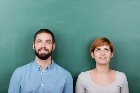 Thoughtful young male and female teachers looking up against chalkboard photo