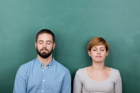 Thoughtful young male and female with closed eyes chalkboard photo